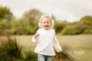 girl running on photoshoot with Chelmsford family photographer Kika Mitchell