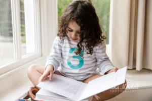 CUTE CHILD FINDING TIME TO PRINT PHOTOGRAPHS AND LOOKING AT PHOTOGRAPH ALBUM BY CHELMSFORD FAMILY PHOTOGRAPHER KIKA MITCHELL PHOTOGRAPHY CHELMSFORD