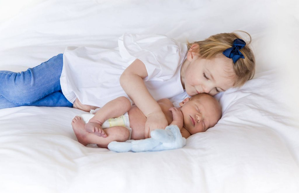 Big sister kissing little baby brother by Kika Mitchell Photography Chelmsford Newborn Photographer