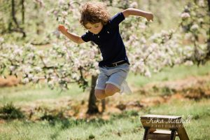 Boy jumps for joy on Spring Blossom photoshoots by Kika Mitchell Photography Chelmsford Photographer