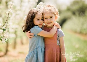 BEST FRIENDS CUDDLING ON SPRING BLOSSOM PHOTOSHOOT AT LATHCOATS BY CHELMSFORD PHOTOGRAPHER KIKA MITCHELL PHOTOGRAPHY