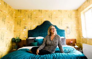 Kika Mitchell Photography has a unique style of personal branding, this shot of TGCO on colourful bedroom portrait of Nicola Lewis laughing on her personal branding shoot by Chelmsford photographer Kika Mitchell Photography