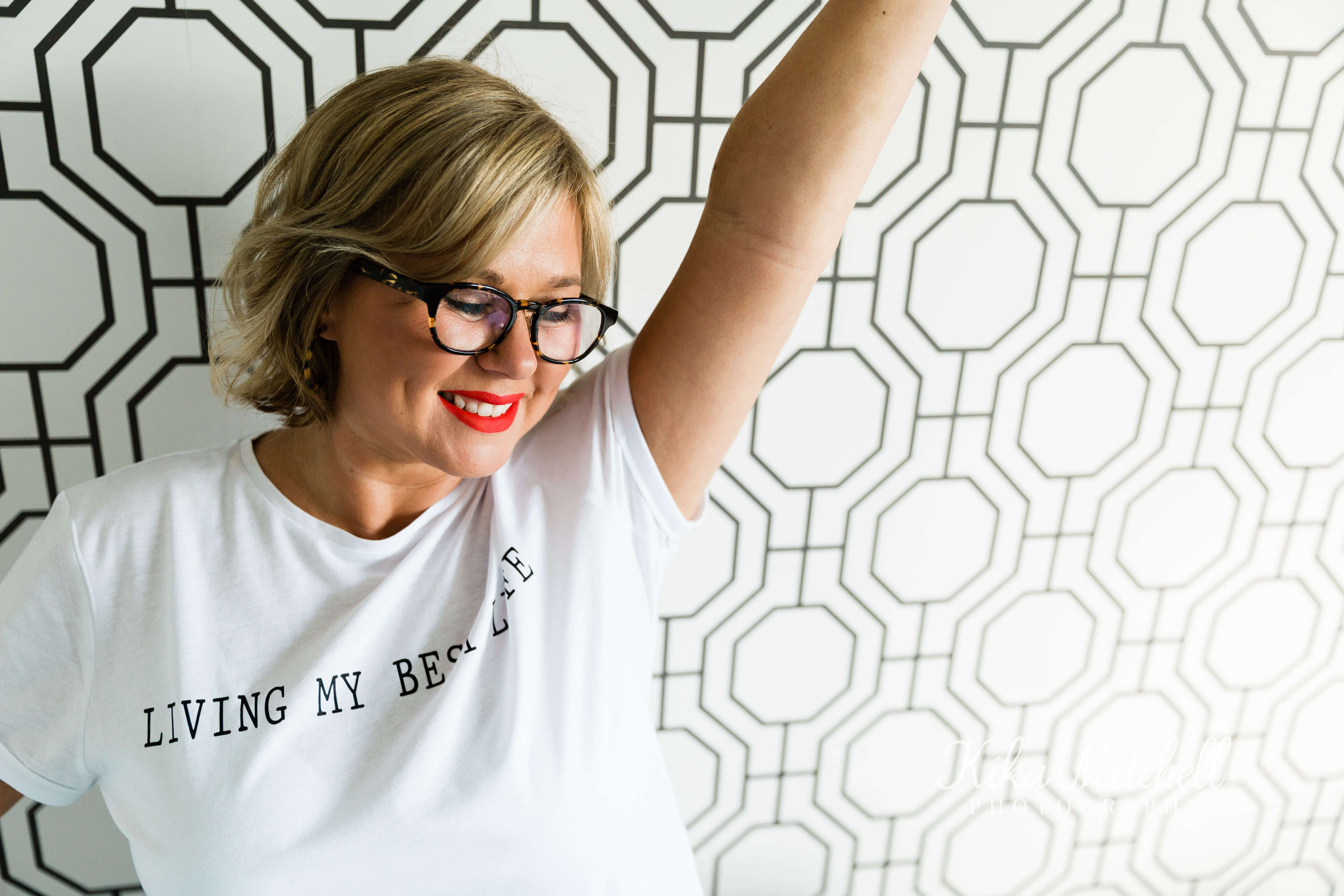 Nicola Lewis of TGCO with arm up on bold graphic wallpaper for personal branding shoot by Chelmsford photographer Kika Mitchell Photographer