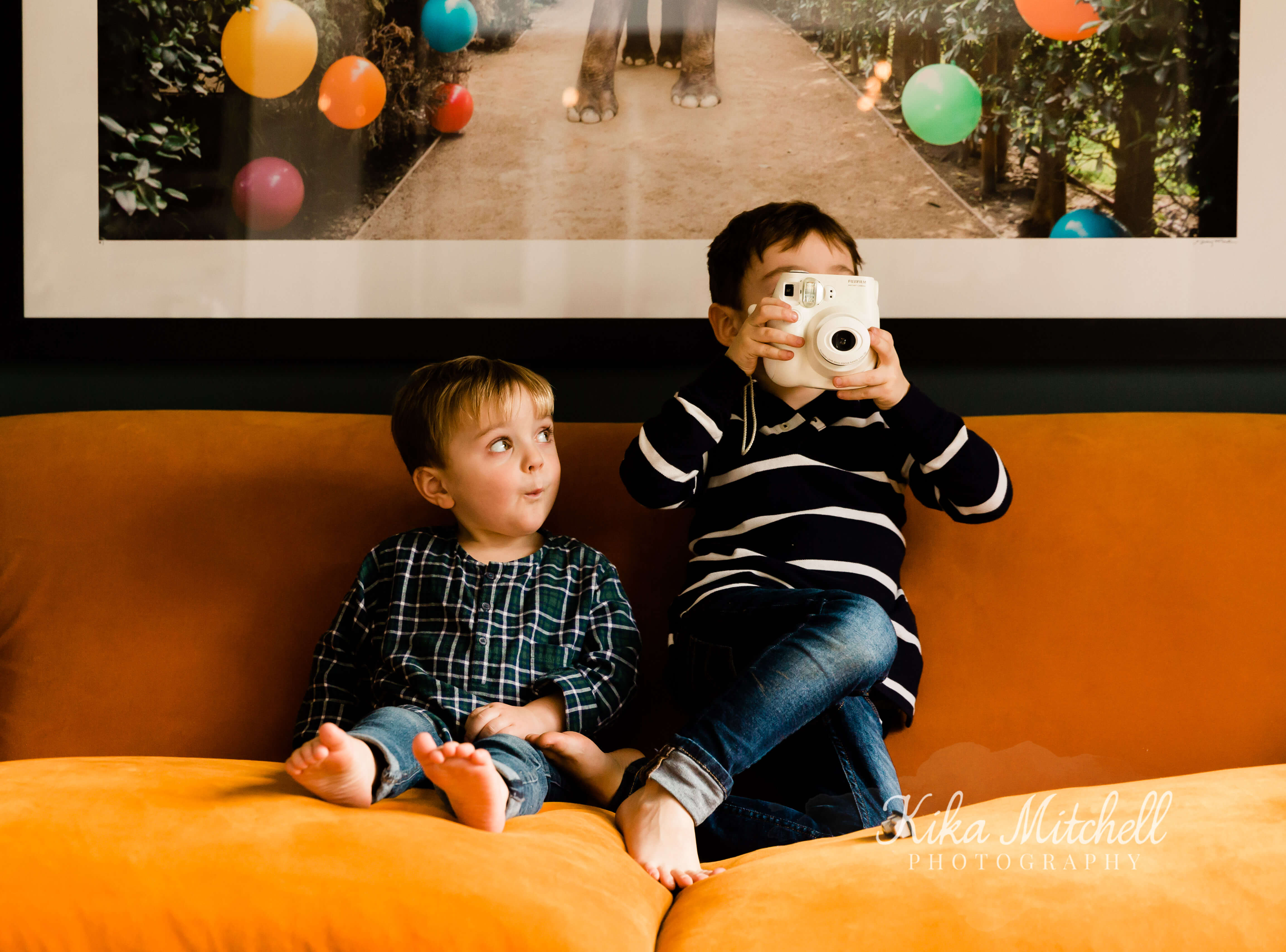 cute image of 2 brothers on orange sofa captured by Chelmsford photographer Kika Mitchell Photography on kitchen renovation inspiration shoot