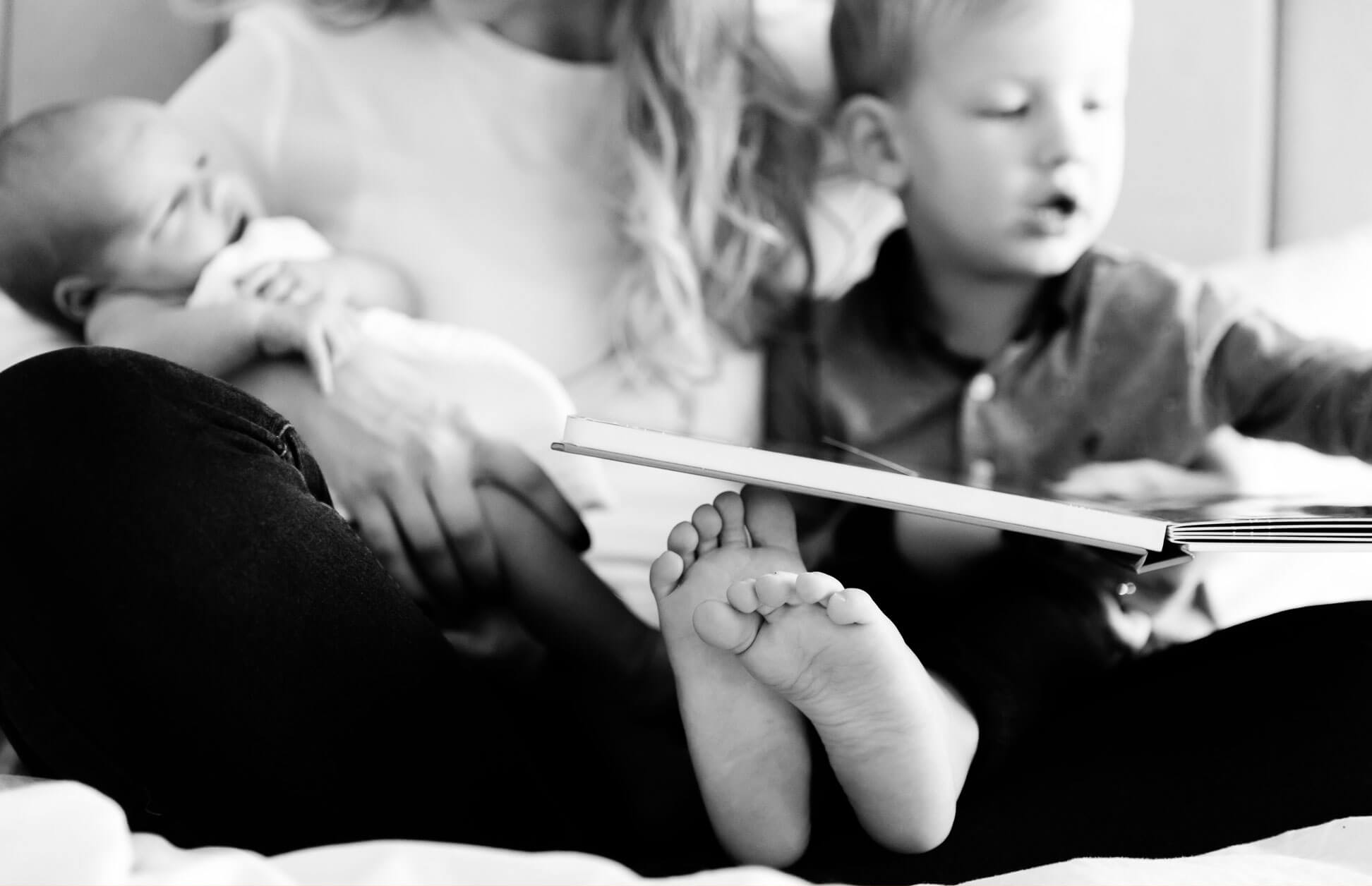 Black and white shot of little boys feet and newborn brother photographed by Chelmsford photographer Kika MItchell Photography
