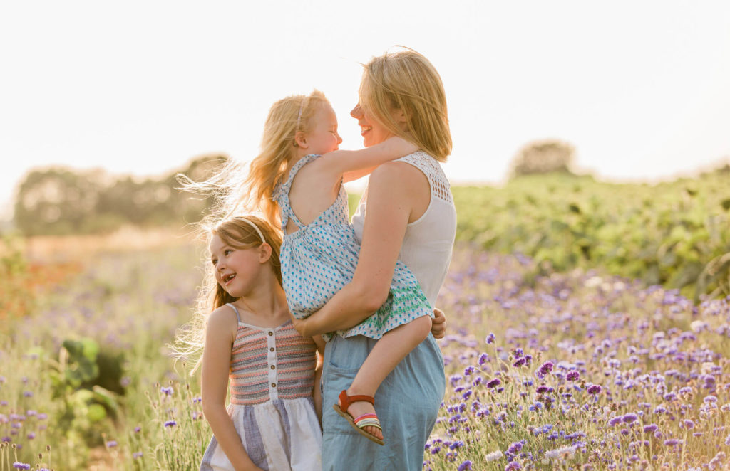 mother and daughters in front of sunset at Writtle Sunflowers captured by Chelmsford family Photographer Kika MItchell photography