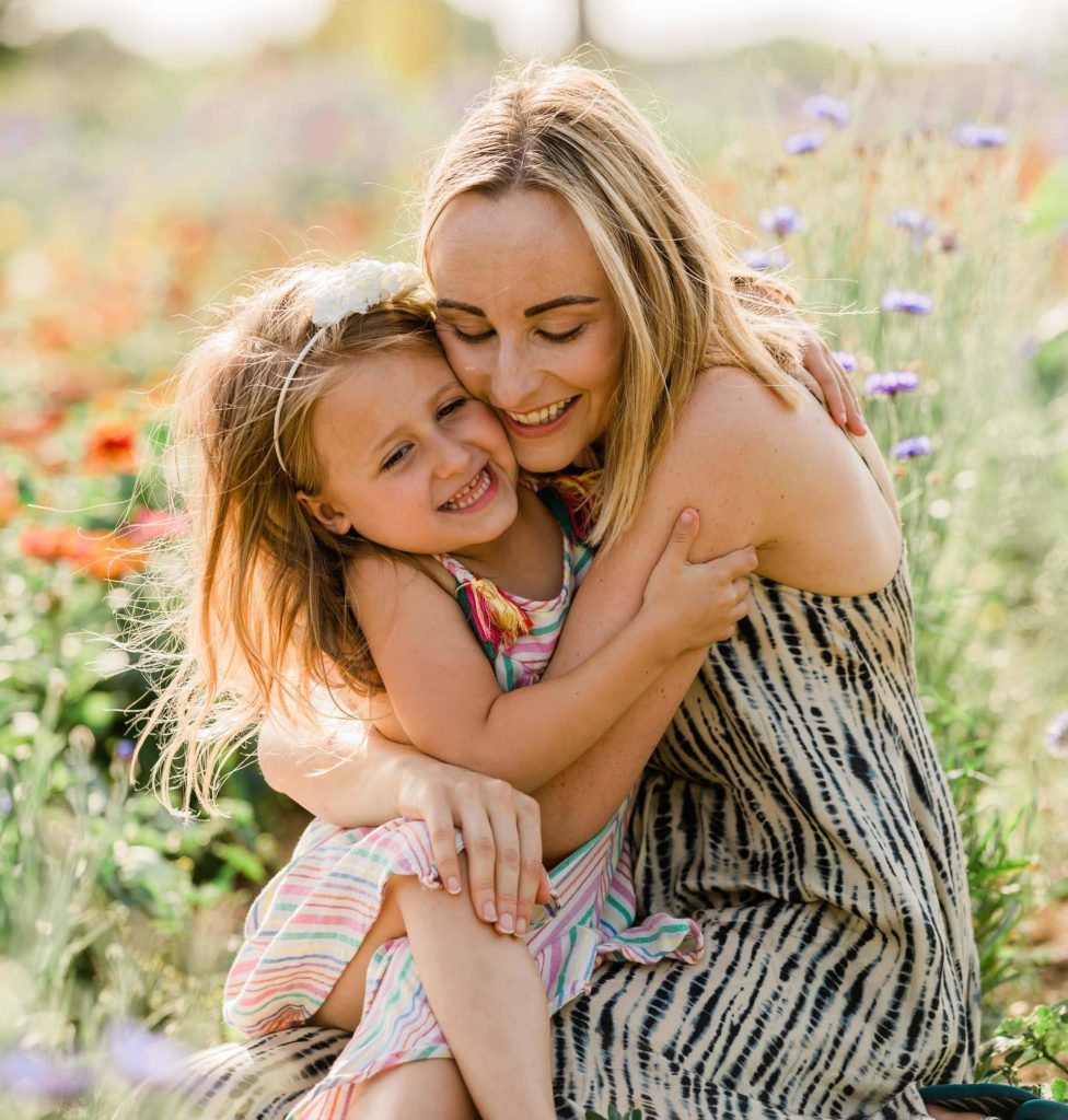 mother and daughter embrace in summer flower meadow with flowers behind captured by Chelmsford photographer Kika Mitchell Photography