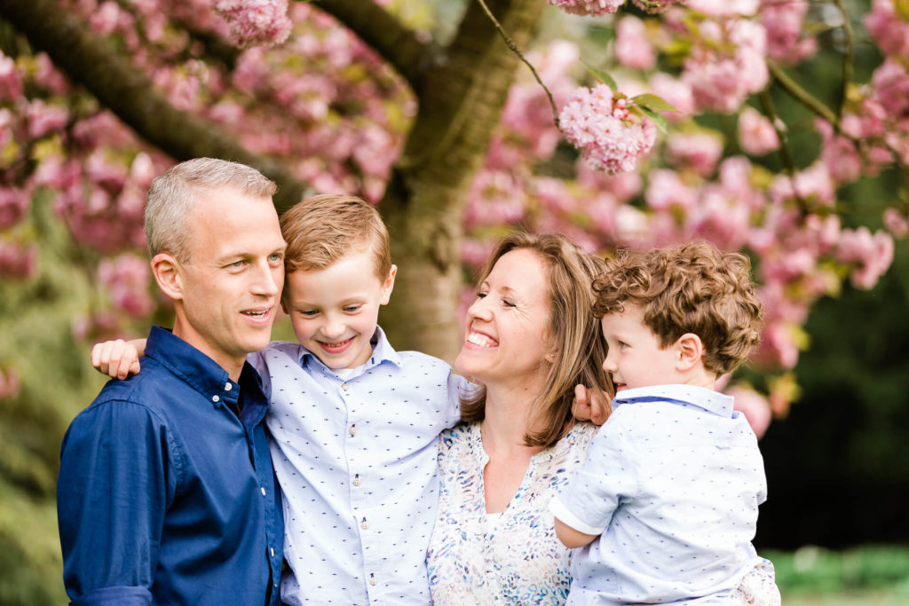 family of 4 with blossom tree background, mother smiling at Hylands Park Essex captured by Chelsmsford photographer Kika Mitchell Photography