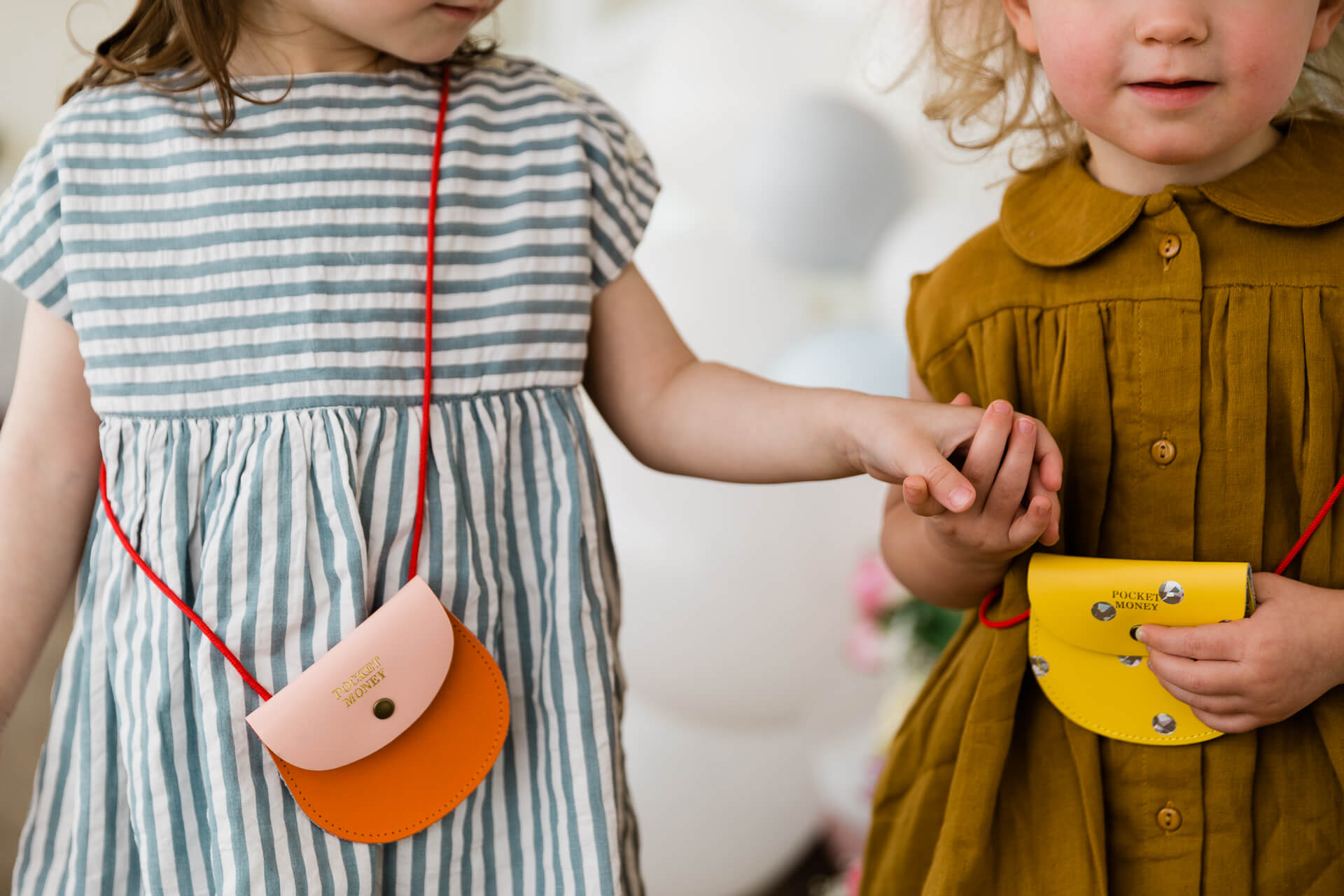 little girls holding hands with pocket money purses photographed on Fable and Moon Easter shoot by Chelmsford photographer Kika MItchell photography