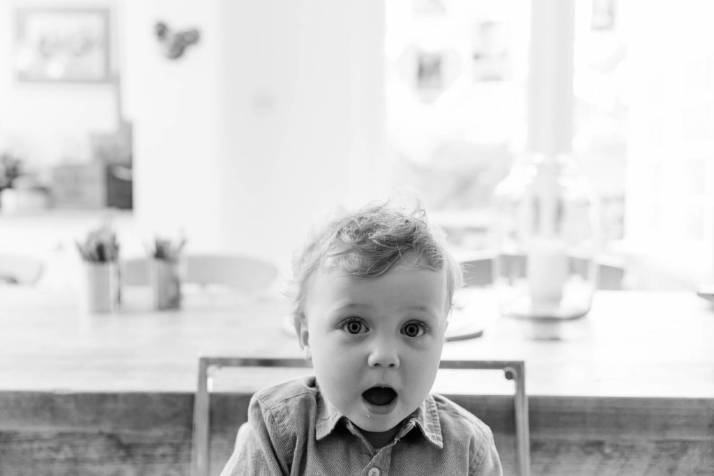 black and white image of toddler with mouth open in front of window capture by Chelmsford family photographer Kika Mitchell Photography
