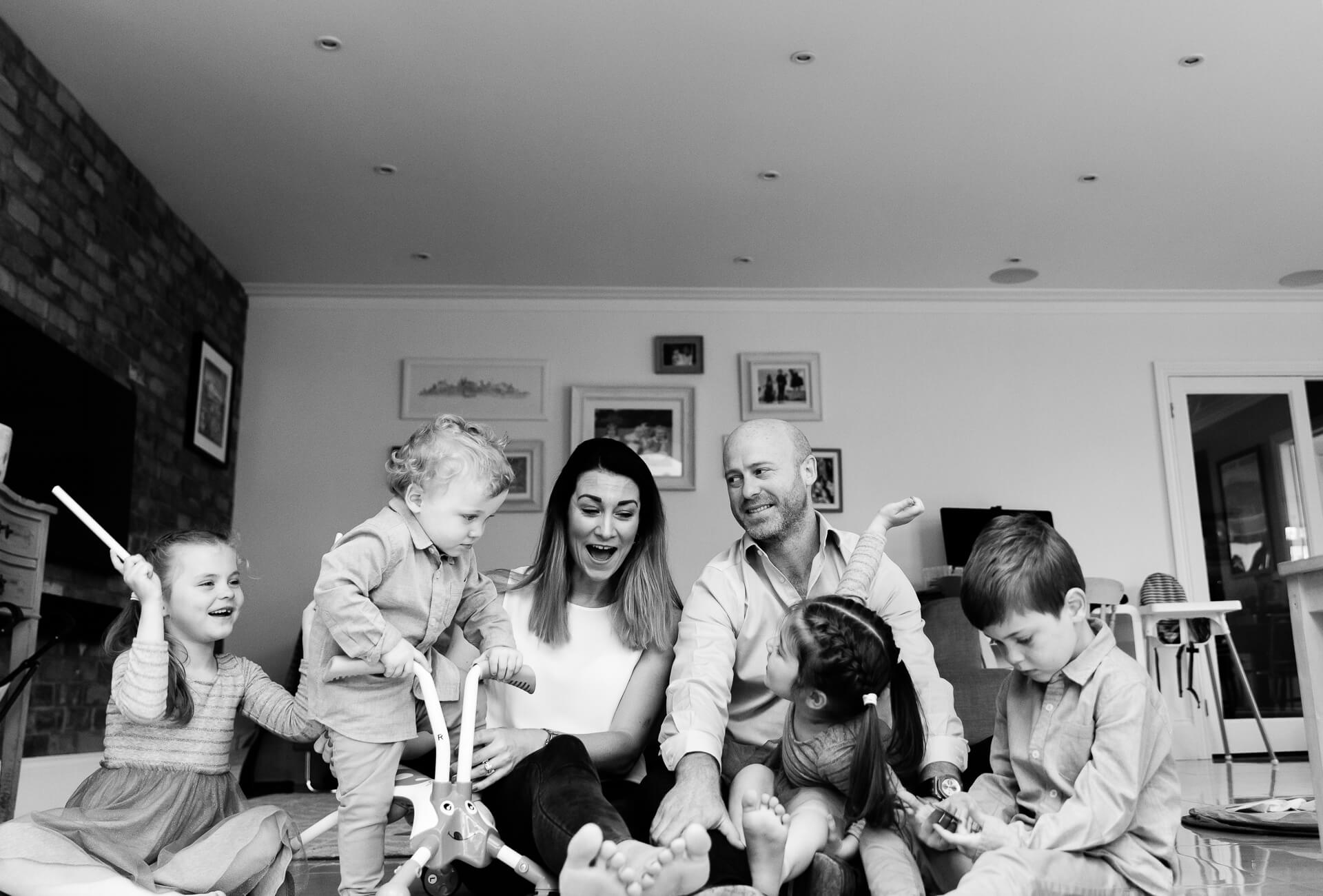 family of 6 all sat on floor having fun, mum laughing captured by Chelmsford family photographer Kika Mitchell Photography