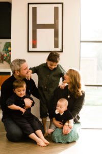 Fun relaxed shot of family of 5 in front of H letter poster captured by Chelmsford photographer Kika Mitchell Photography