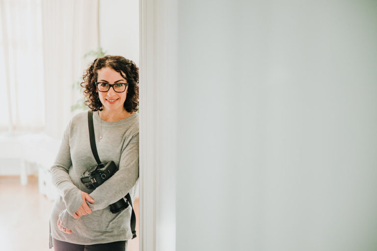 Chelmsford photographer Kika Mitchell Photography standing in doorway with camera on personal branding shoot at home