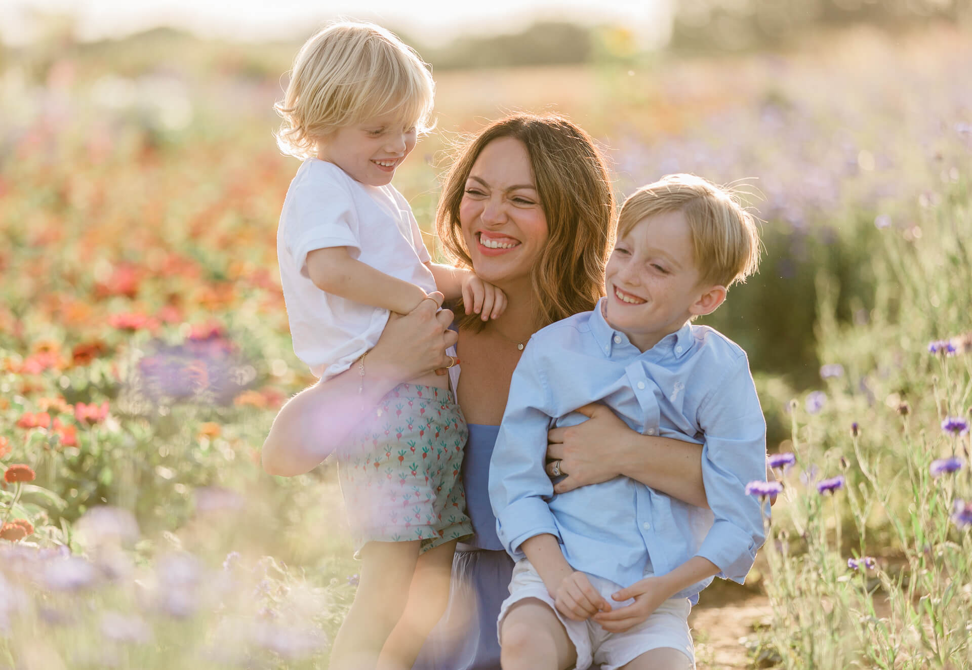 Pricing Chelmsford photographer featuring Mother and happy boys at sunset in flower meadow on Pricing page information by Chelmsford photographer Kika Mitchell Photography