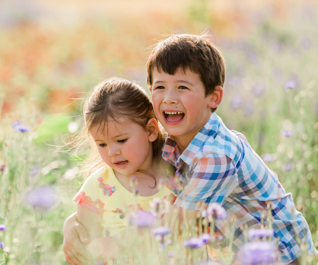 brother and his sister in the flower meadow at sunset captured by Chelmsford family photographer Kika Mitchell photography