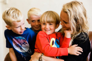 mother cuddles her 3 blonde boys at home on family shoot photographed by Chelmsford family photographer Kika Mitchell Photography