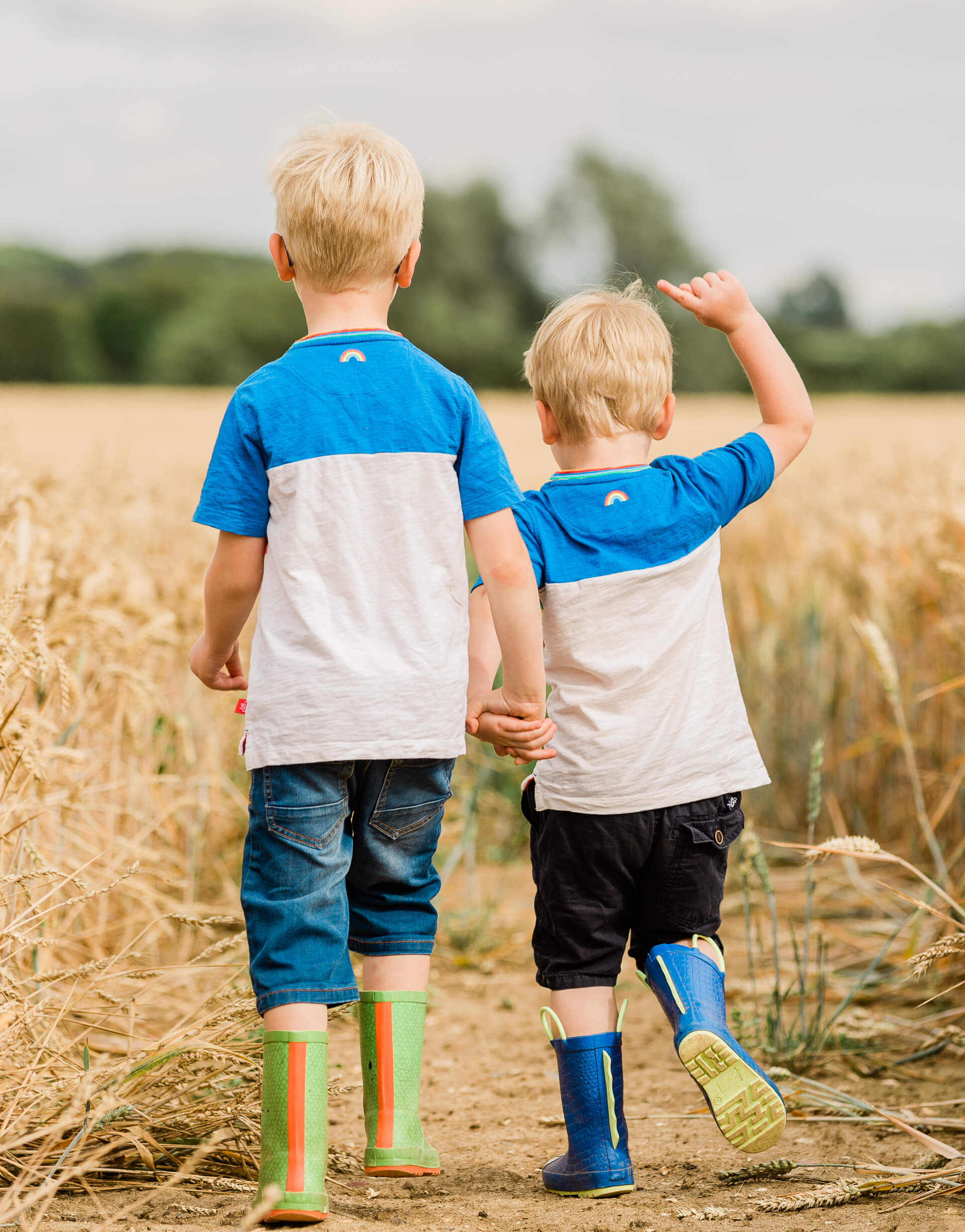 Young brothers in corn field walking away from camera in matching clothes captured by Chelmsford family photographer Kika Mitchell Photography