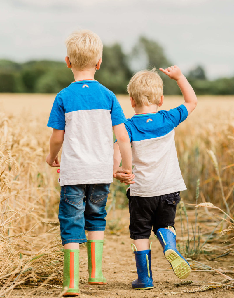 Young brothers in corn field walking away from camera in matching clothes captured by Kika Mitchell Photography