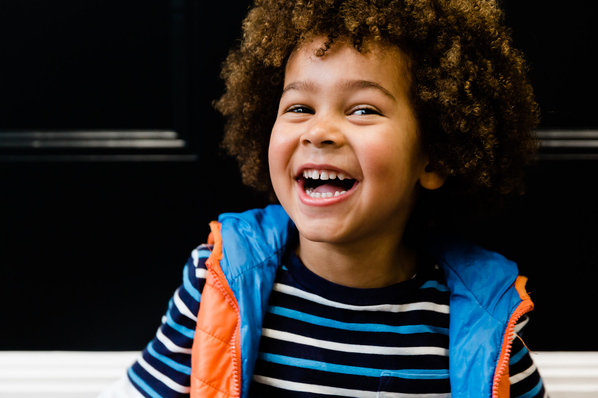Gorgeous smiling boy with afro in Child modelling headshots by Chelmsford photographer Kika Mitchell Photography Essex