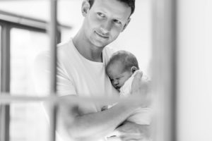 Black and white image of Father and son in mirror reflection captured by Chelmsford Newborn photographer Kika Mitchell Photography