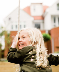 little blonde girl on swing looks back in glee photographed by Chelmsford photographer Kika Mitchell Photography Chelmsford photographer