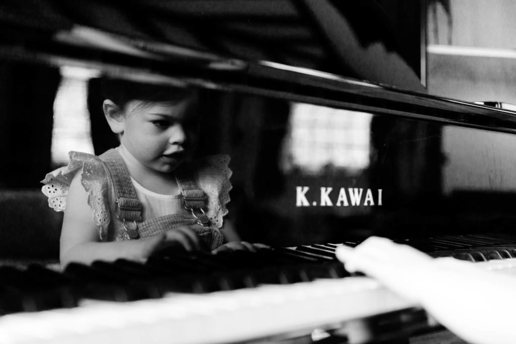 My style of monochrome image of little girl playing a grand piano in Black Notley captured by Chelmsford photographer Kika Mitchell Photography