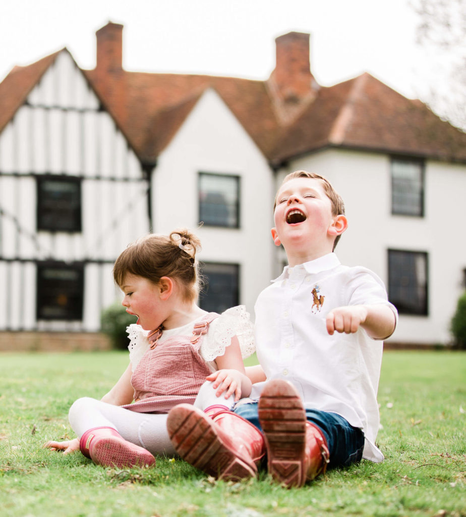 laughing siblings sat in front of the oldest farm in Black Notley in Essex captured by chelmsford photographer Kika mitchell Photography