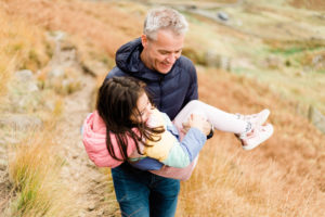 joyful father carries daughter on mountainside captured by Chelmsford photographer Kika Mitchell Photography