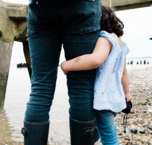 My style of family portrait, little girl holds onto her daddy at the beach captured by me Chelmsford photographer Kika Mitchell photography