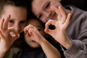 young boys making shapes with their hands taken by Chelmsford photographer Kika Mitchell in Brentwood