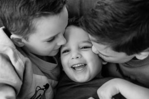 laughing kisses and cuddles in black and white image on latest family photoshoot of Emily Norris family by Chelmsford photographer Kika Mitchell Photographer