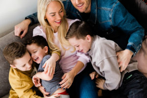 laughing family of 5 on sofa on Emily Norris's latest family shoot by Chelmsford photographer Kika Mitchell Photography