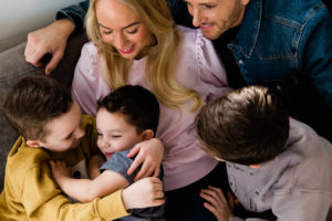 young son enjoys big cuddles from his family in loving portrait captured by Essex photographer Kika Mitchell on Emily Norris's latest family shoot