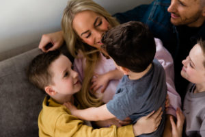 family cuddle on sofa, all looking at youngest son Jackson taken by Chelmsford photographer Kika Mitchell Photography