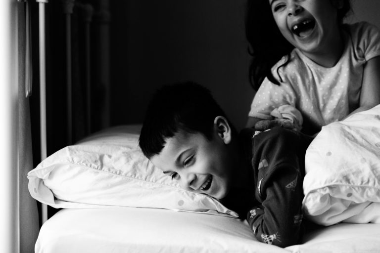 monochrome image of brother and sister in bed, gappy laughter captured by Chelmsford Photographer Kika Mitchell Photography