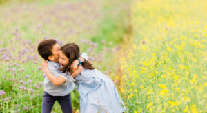 children hugging in bright flower meadow captured by Chelmsford photographer Kika Mitchell Photographer