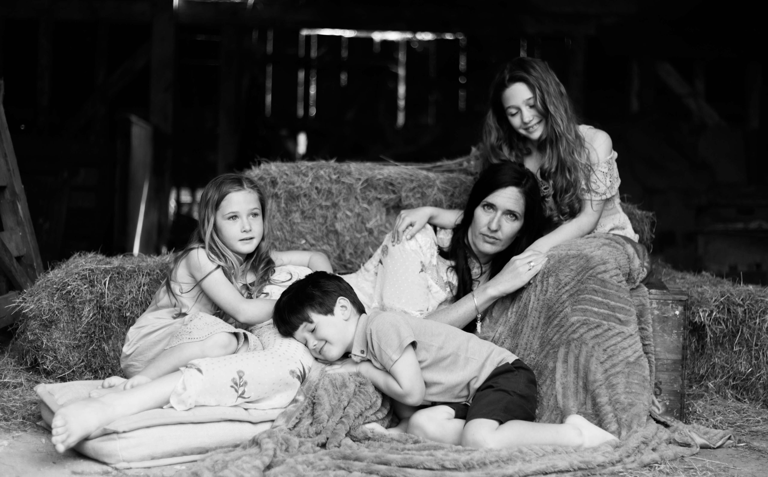 serious portrait of motherhood in black and white in barn by Chelmsford photographer Kika Mitchell