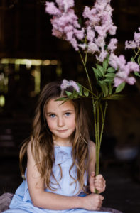 young girl in blue holds purple flowers whilst looking to camera captured by Chelmsford photographer Kika mItchell photography