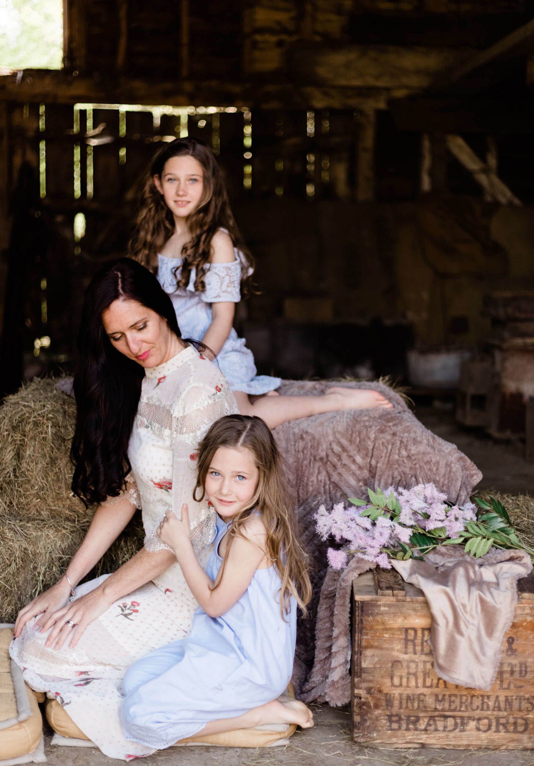 portrait of a mother looking down whilst 2 daughters look to camera in barn by Chelmsford photographer Kika mItchell Photography
