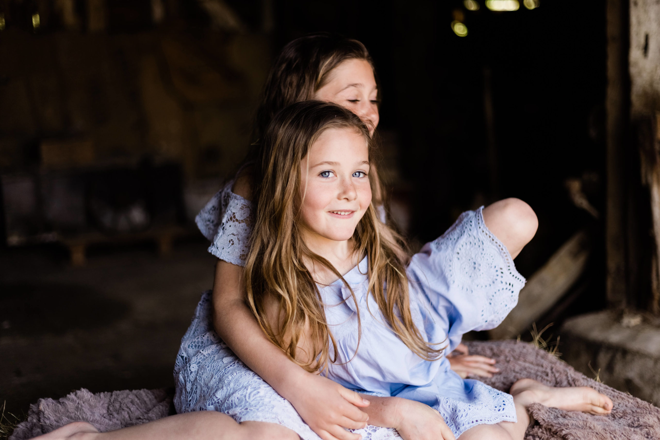 2 sisters in blue sat on hay bale captured by Chelmsford Kika Mitchell photography
