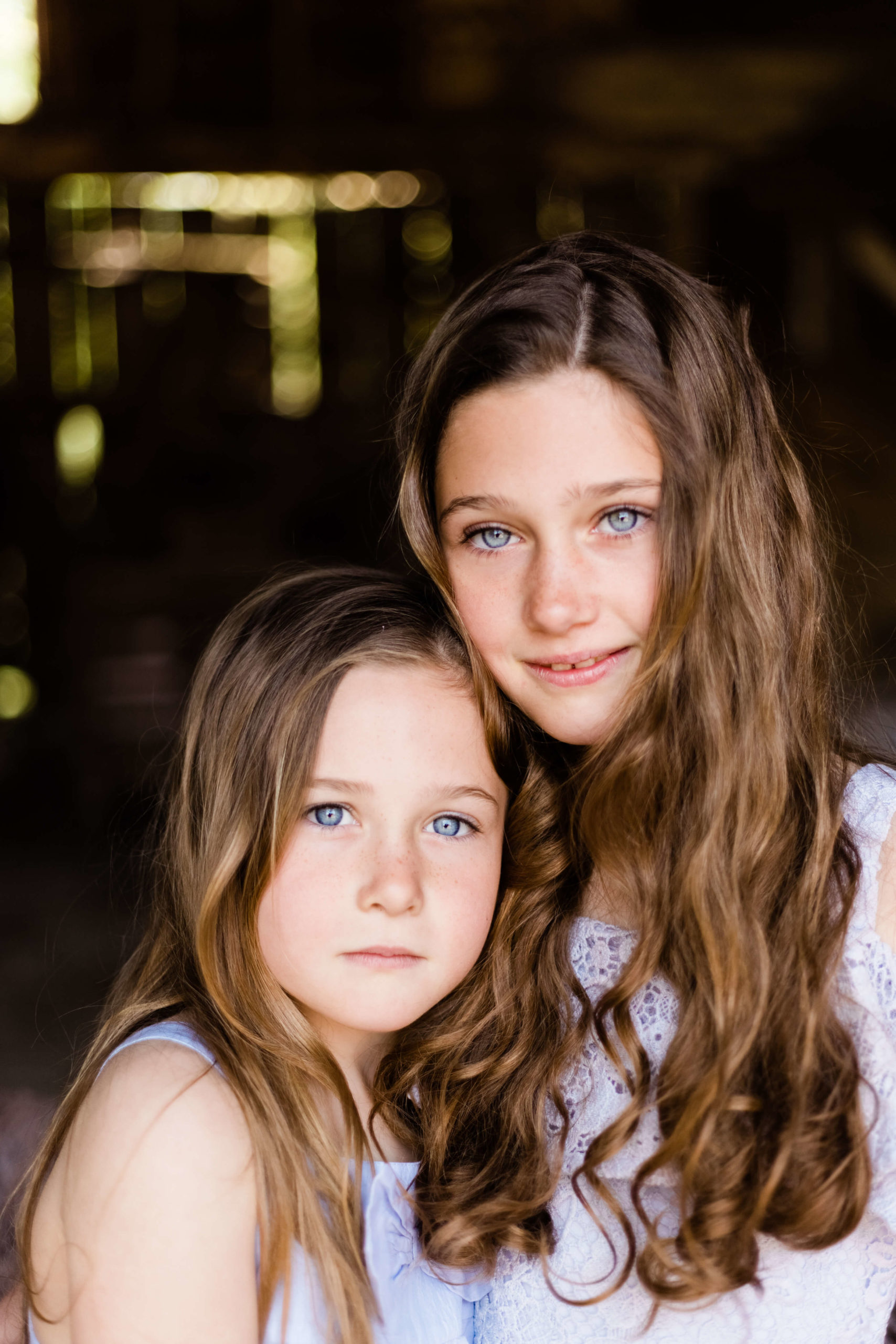 2 sisters looking to camera in mid close up in portrait of motherhood by Kika Mitchell photography