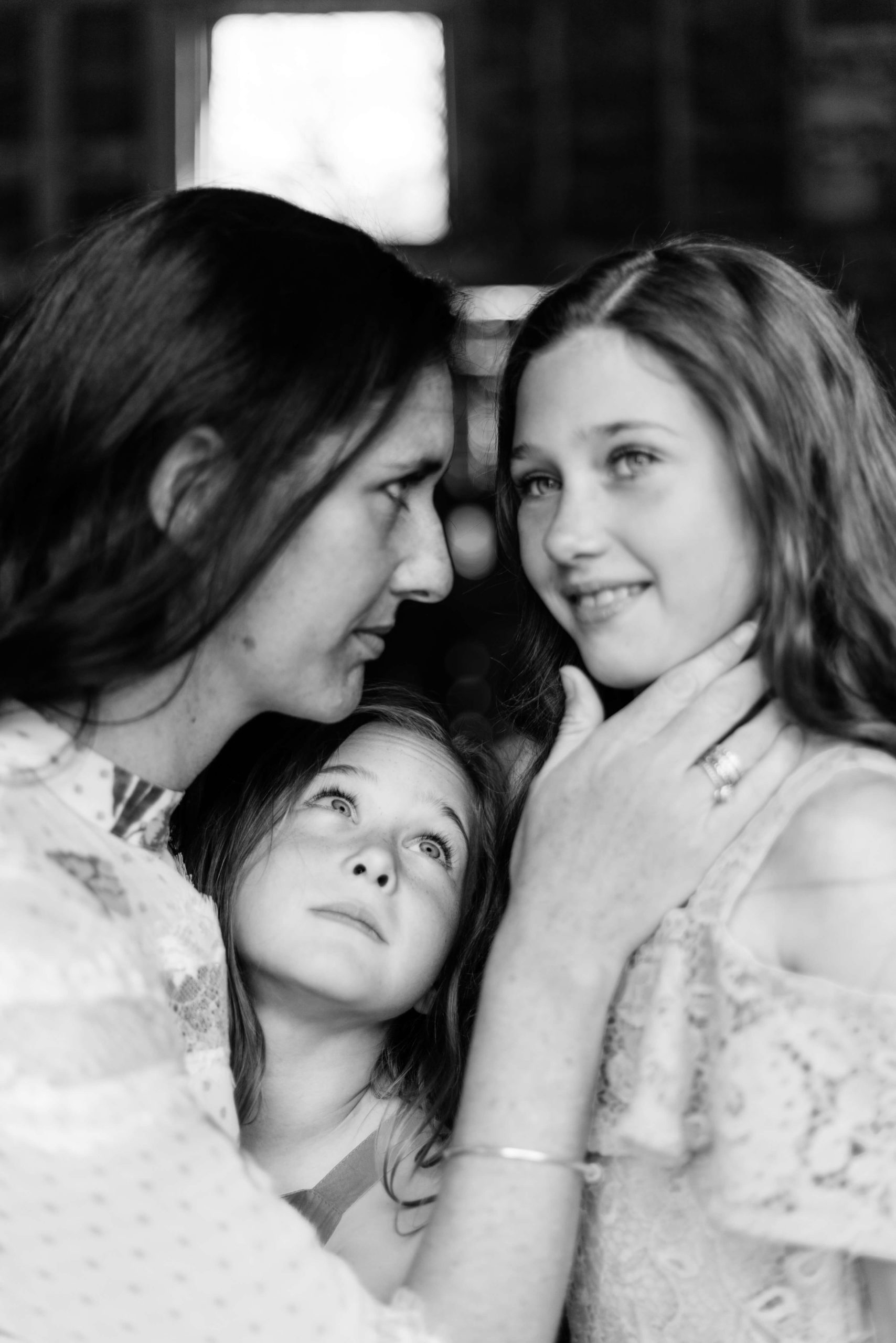 mother holds daughter's face as other daughter gazes at her sister in monochrome portrait of motherhood by Kika Mitchell photography Chelmsford photographer