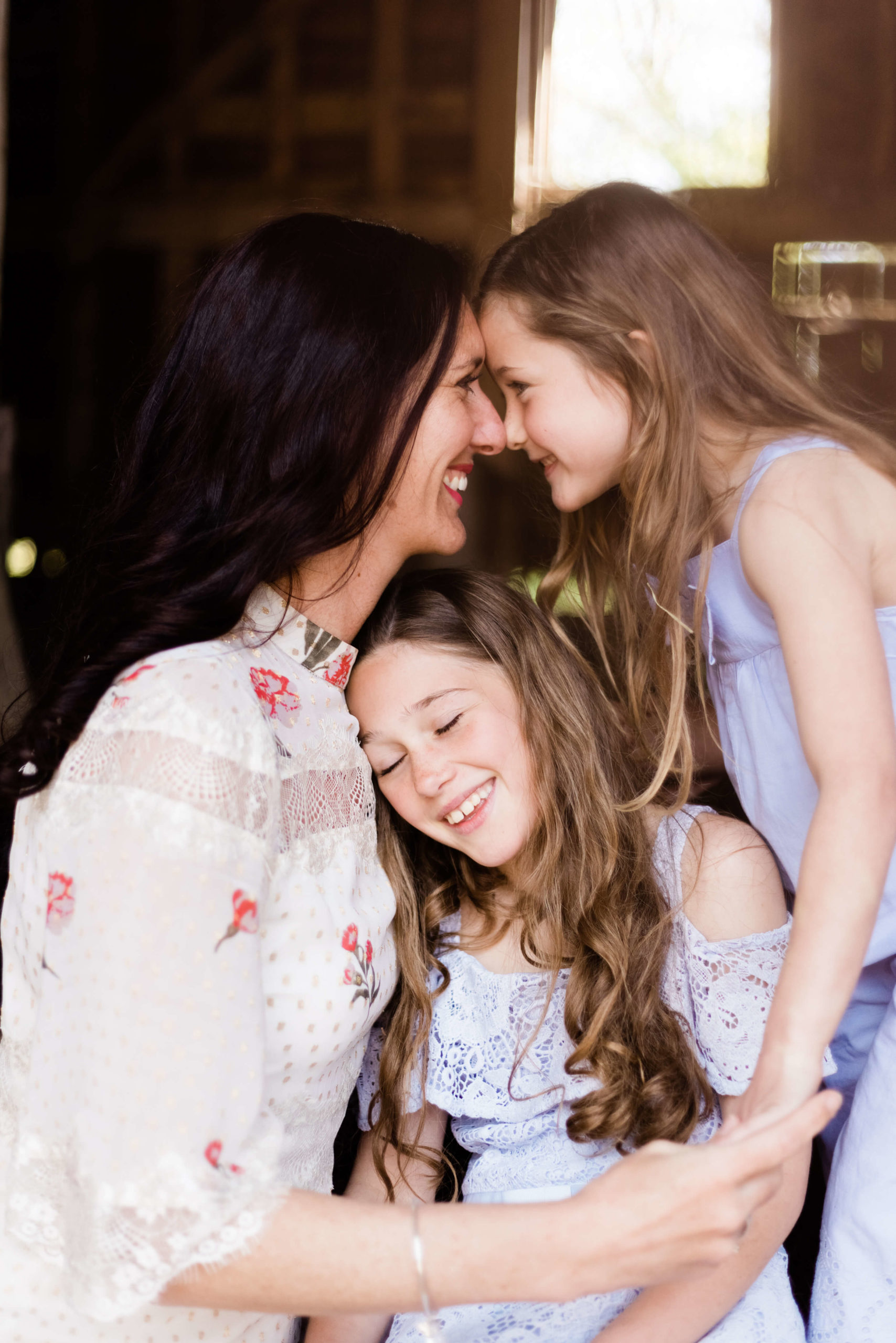 portrait of motherhood featuring mother and 2 beautiful daughter, one in middle and one getting an eskimo kiss by Chelmsford photographer Kika Mitchell photographer