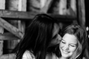 black and white image of mother and daughter, daughter crinkles nose as mother kisses her by chelmsford photographer Kika mitchell photography