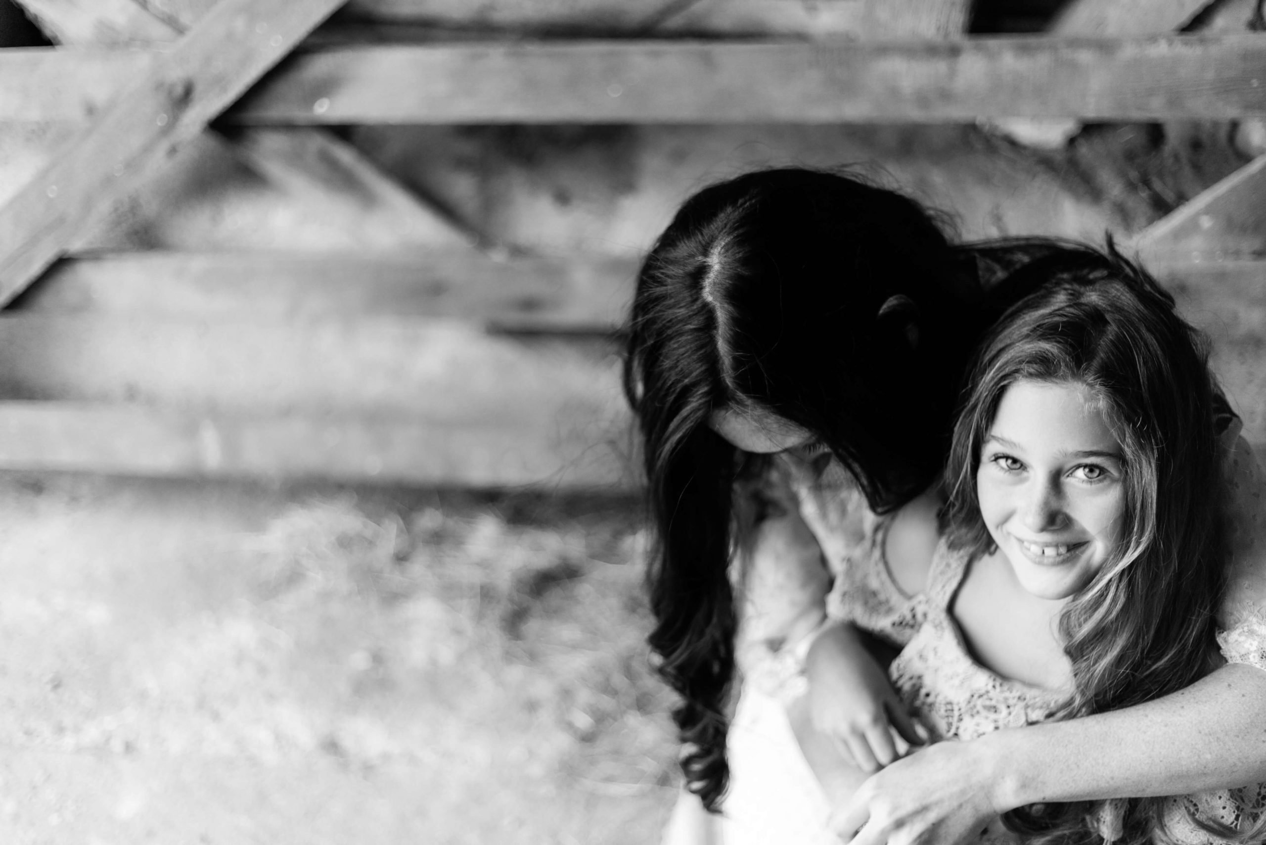 black and white image of mother and daughter by gate, girl looks to camera and mum looks down by Chelmsford photographer Kika mitchell photography