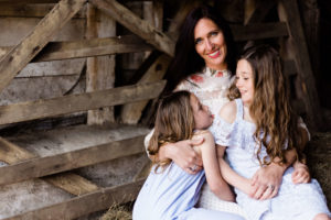 portrait of motherhood by Kika Mitchell Photography, mother holds her daughters and looks to camera